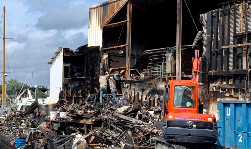 Photo by Mikaela EsauWorkers labor to clear post-fire wreckage.
