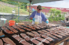 Photo courtesy Judy Benson/Conn. Sea GrantA worker readies planked shad for the fire at a Rotary Club Shad Bake in Essex, Connecticut.