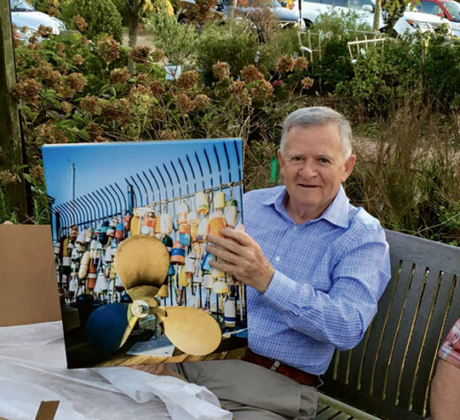 Larry Cannon poses with an image of the gate at his Boston Waterboat Marina on Long Wharf where the author also has his shop. The iconic lobster buoys are a popular backdrop for visiting tourists. Photo courtesy Christopher Birch