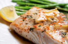 Fresh halibut filet, pan seared with lemon butter and artichoke on top, asparagus on the side.