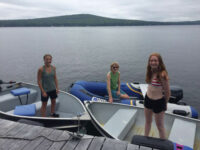 Photo courtesy Tim PlouffProud and independent MIah and Addison pose in their respective boats at the dock with Kathy in the inflatable in the background.